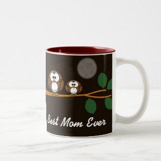 Cute owl with baby on green tree in moon light coffee mug
