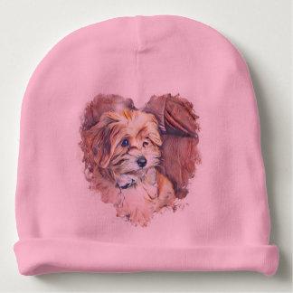 Cute puppy in a heart baby hat