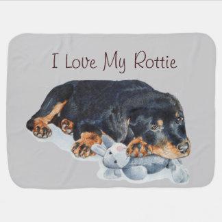 cute puppy rottweiler cuddling grey teddy bear swaddle blanket