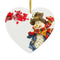 Cute snowman figurine with red berries on white ceramic ornament