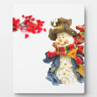 Cute snowman figurine with red berries on white plaque