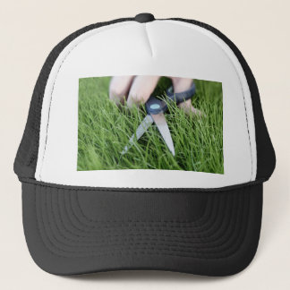 Cutting the grass with a pair of scissors trucker hat