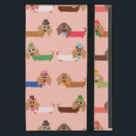 "Dachshunds on Pink iPad Mini Cover<br><div class=""desc"">Dachshunds on Pink, an adorable dog design that dog lovers, especially Dachshund lovers, will find too cute to resist! Features Dachshunds in sweaters of chocolate brown, green, blue, coral, pink, and white, some wearing eye glasses, some with bows or even top hats! This cute dachshund design is available on bags,...</div>"