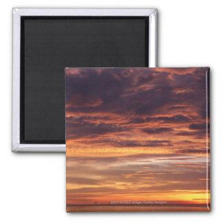 Dark clouds in orange streaked sky magnets