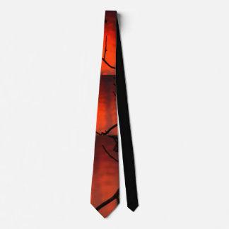 Dark orange sunset with black branches tie