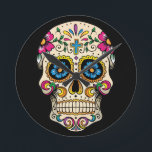 """Day of the Dead Sugar Skull with Cross Round Clock<br><div class=""""desc"""">Sugar skulls are very trendy!  A colorful day of the dead sugar skull with pretty flowery details.  Gothic spooky skeleton imagery.  Great urban art.  Customize by adding text and/or changing the background color.     Day of the dead vector image extended license from Fotolia.com - &#169; tairygreene - Fotolia.com.</div>"""