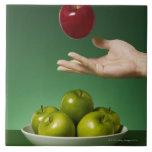 dé lanzar la manzana roja en el aire y el verde azulejos