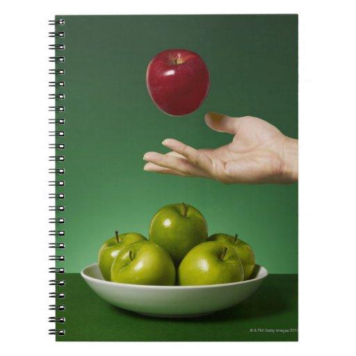 dé lanzar la manzana roja en el aire y el verde libreta espiral