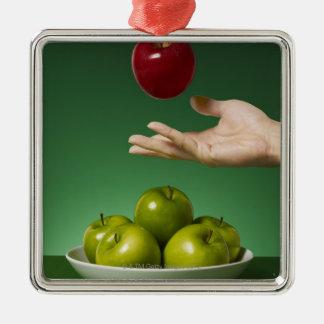 dé lanzar la manzana roja en el aire y el verde adorno cuadrado plateado