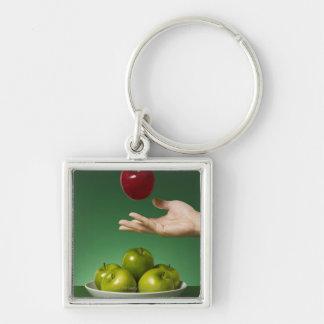dé lanzar la manzana roja en el aire y el verde llavero cuadrado plateado