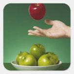 dé lanzar la manzana roja en el aire y el verde pegatina cuadrada