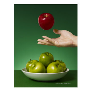 dé lanzar la manzana roja en el aire y el verde postales