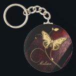 """Dear Butterfly ID199 Keychain<br><div class=""""desc"""">A golden butterfly and swirls dominate this design on a background that has the tone of rich,  oxblood leather. Change text to your own name or initials using the easy template.</div>"""