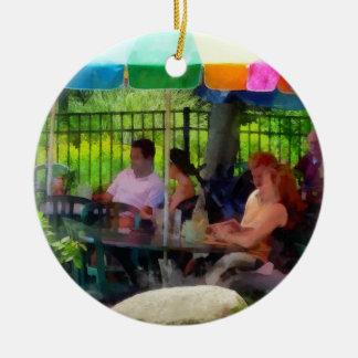 Debajo de los paraguas coloridos adorno navideño redondo de cerámica