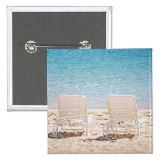 Deck chairs on sandy beach pinback button