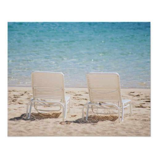 Deck chairs on sandy beach poster