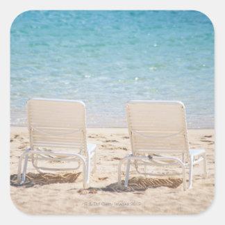 Deck chairs on sandy beach square sticker
