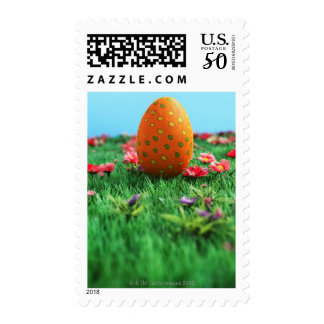 Decorated Easter egg amongst flowers on grass, Postage