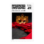 Decorated mask for masquerade on red velvet postage stamp