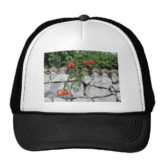Decorative stone wall with colorful flowers trucker hat