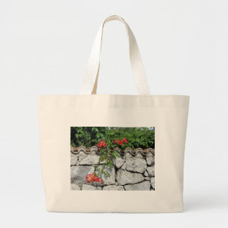 Decorative stone wall with colorful flowers large tote bag