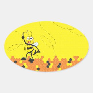 Dedo amarillo lindo de la abeja que señala encima pegatina ovalada