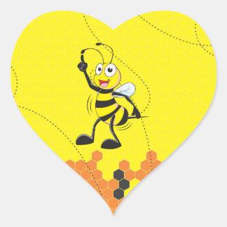 Dedo amarillo lindo de la abeja que señala encima pegatina en forma de corazón