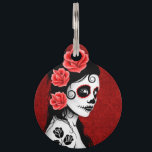 "Deep Red Day of the Dead Sugar Skull Girl Pet Tag<br><div class=""desc"">This Day of the Dead inspired design features a beautiful woman with sugar skull patterns on her face. Three roses appear in her jet black hair with two more roses tattooed on her arm. The girl is standing sideways with her head turned slightly towards the viewer. Her pure white skin...</div>"