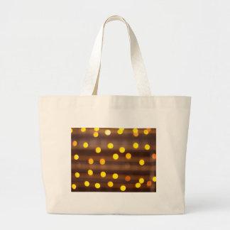Defocused and blur image of yellow round light bul large tote bag