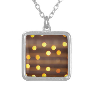 Defocused and blur image of yellow round light bul square pendant necklace