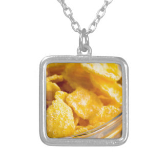 Defocused and blurred image of dry corn flakes silver plated necklace