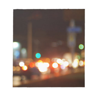 Defocused image of traffic on night city street notepad
