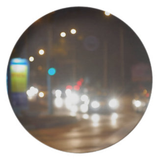 Defocused lights on the stream of cars and traffic plate