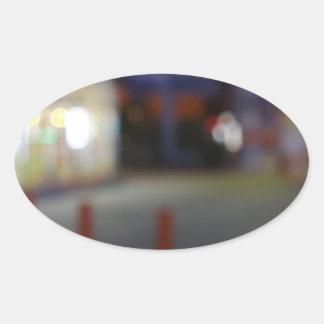 Defocused night urban scene with blurred lights oval sticker