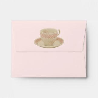Del sobre blanco y rosado de la taza de té