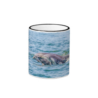 Delfín del amor de madre y taza del bebé