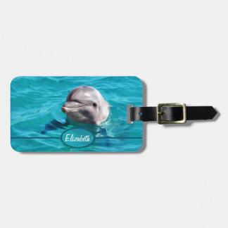 Delfín en foto del agua azul etiquetas maleta