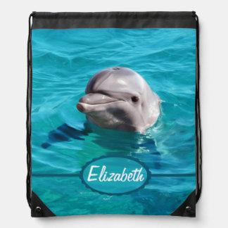 Delfín en foto del agua azul mochila
