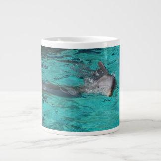delfín que sale de la página llena del agua del tr taza grande