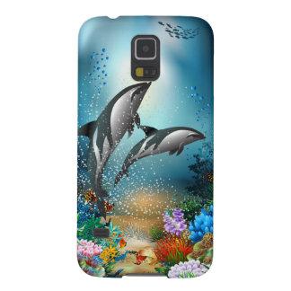 Delfínes de los pares que juegan en el océano
