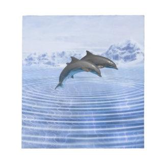 Delfínes en el mar azul claro blocs