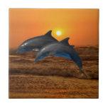 Delfínes en la puesta del sol azulejos