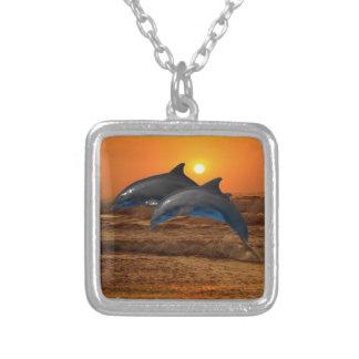 Delfínes en la puesta del sol colgante cuadrado