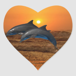 Delfínes en la puesta del sol pegatina en forma de corazón