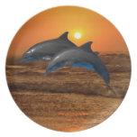 Delfínes en la puesta del sol platos