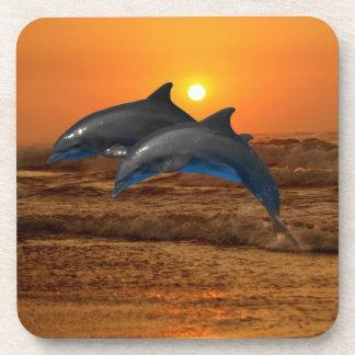 Delfínes en la puesta del sol posavasos de bebida