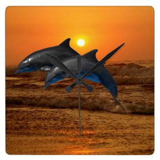 Delfínes en la puesta del sol reloj cuadrado