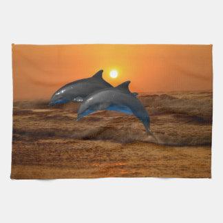 Delfínes en la puesta del sol toalla de cocina