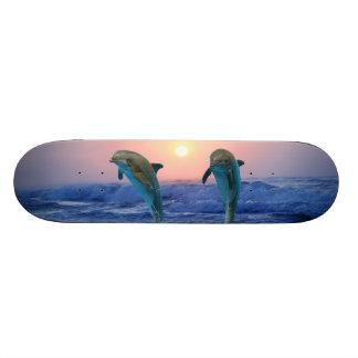 Delfínes en la salida del sol monopatin