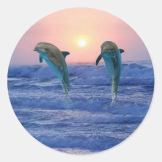Delfínes en la salida del sol pegatina redonda
